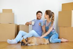 Happy couple with boxes and dog moving to new home. Mortgage, people and real estate concept - happy couple with boxes and french bulldog dog moving to new home royalty free stock photography