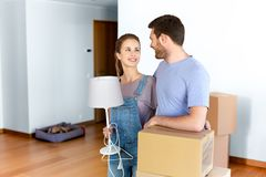 Couple with boxes and lamp moving to new home Stock Photography
