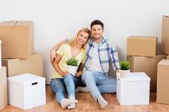 Happy couple with boxes moving to new home. Mortgage, people and real estate concept - happy couple with boxes moving to new home royalty free stock photo
