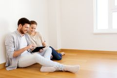 Happy couple with tablet pc computer at new home. Mortgage, people and real estate concept - happy couple with tablet pc computer at empty room of new home Stock Photos