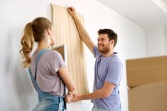 Couple with wallpaper repairing apartment or home Stock Photo