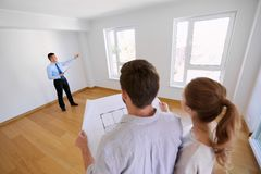 Realtor showing new home to couple with blueprint Stock Image