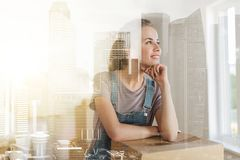 Happy woman with box moving to new home. Mortgage, people and real estate concept - happy women with box moving to new home over city buildings background and Royalty Free Stock Images