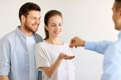 Realtor giving keys from new home to happy couple Stock Images