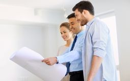 Realtor showing blueprint of new home to couple Stock Photo