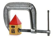 Mortgage Pressure. Toy house squeezed in a vice Stock Image