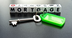 Mortgage. Text ' mortgage '  on small white cubes in black uppercase letters with key and green tag Stock Photos