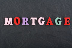 MORTGAGE word on black board background composed from colorful abc alphabet block wooden letters, copy space for ad text. Word on black board background composed royalty free stock photos