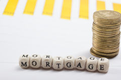 MORTGAGE word written on wood block, golden coins and chart Royalty Free Stock Photos