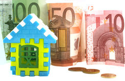 Mortgages in foreign currency concept. Model home is on the background of euro banknotes Royalty Free Stock Photography