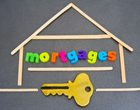 Mortgages; house loans. A closeup image of a stylized house with the word mortgages in colorful lower case letters and a gold key. The image is designed as a Stock Image