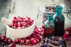 Mortier avec les bourgeons roses, les bouteilles de teinture et les fleurs sèches photos libres de droits