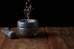 Mortier de marbre sur la vieille table en bois sur le fond noir avec l'espace de copie Les graines de poivre tombent dans le mort photos libres de droits