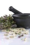 Mortier en céramique, thym et pillules de fines herbes Photo stock
