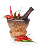 Mortier en stamper met roodgloeiende Spaanse peperpeper en peperbollen royalty-vrije stock foto