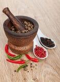 Mortier en stamper met roodgloeiende Spaanse peperpeper en peperbollen royalty-vrije stock afbeeldingen