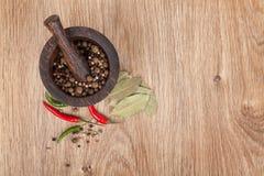 Mortier en stamper met roodgloeiende Spaanse peperpeper en peperbollen stock afbeeldingen