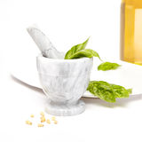 Mortier et pilon de marbre blancs et gris avec des ingrédients pour le pesto, le basilic, les pignons, et l'huile d'olive Images libres de droits