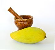 Mortier et pilon en bois avec la mangue jaune Images stock
