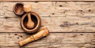 Mortier et pilon tenus dans la main en bois photographie stock libre de droits