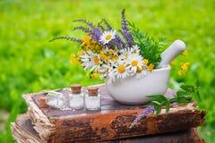 Mortier van in openlucht het helen van kruiden, flessen van homeopathische druppeltjes en oud boek stock foto's