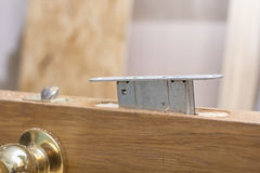 Mortise lock is inserted halfway into the wooden door. Stock Image