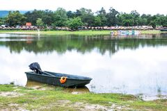 Motorboat and orange life jacket beside lake with rafts, pedal boat background at Chiangmai.Thailand. Motorboat and orange life jacket beside lake with rafts stock photo