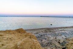 Morze Śródziemnomorskie w promieniach położenia słońce Pian fala i Denny piasek Zdjęcia Stock