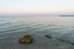 Morze Śródziemnomorskie w promieniach położenia słońce Pian fala i Denny piasek Zdjęcie Stock