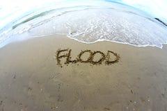 Morze fala która wymazuje słowo powódź na Dennej plaży Obraz Stock
