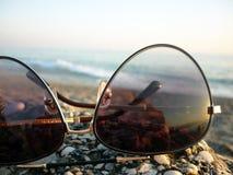 Morze i plaża w słońc szkłach Fotografia Stock