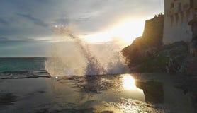 Morze który rozbija z kiścią przeciw słońcu zdjęcia stock