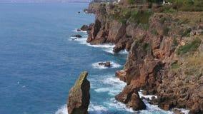 Morze macha bicie przeciw skałom na tle miasta i gór widok od above zbiory wideo