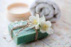 Morze sól, piękno śmietanka z jaśminowym kwiatem i biali ręczniki na drewnianym stole, Fotografia Stock