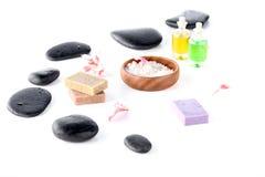 Morze sól w pucharze, czarnych zdrojów kamieniach i storczykowych płatkach odizolowywającym na bielu, Obrazy Stock