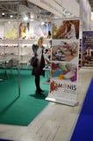 Mos Москвы обувает выставку специализированную International для обуви, сумок и женщина аксессуаров выбирает ботинки Стоковое фото RF