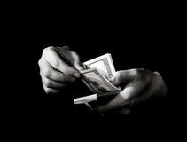 Mãos com dólares sobre o preto Fotos de Stock Royalty Free