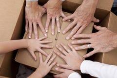 Mãos da família que desembalam as caixas que movem a casa Foto de Stock Royalty Free