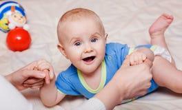 Mãos da matriz pequena da terra arrendada do bebê Fotografia de Stock
