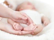 Mãos da matriz que prendem os pés do bebê pequeno Fotos de Stock Royalty Free