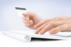 Mãos da mulher que prendem o cartão e a dactilografia de crédito Fotografia de Stock