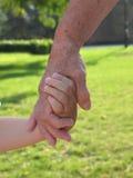 Mãos da terra arrendada da criança e da avó Fotografia de Stock