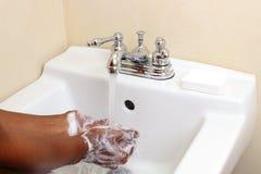 Mãos de lavagem da pessoa preta Fotografia de Stock Royalty Free