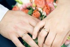 Mãos de pares novo-casados felizes com alianças de casamento e flores do ouro Foto de Stock