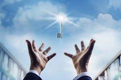Mãos de um homem de negócios que alcança para ao sucesso chave, conceito do negócio Fotografia de Stock