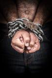 Mãos de um homem descamisado acorrentado com uma corrente e um cadeado Fotografia de Stock