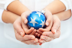 Mãos do adulto e da criança que prendem o bauble do Natal Foto de Stock Royalty Free
