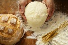 Mãos do cozinheiro chefe com massa e pão orgânico natural caseiro e farinha Fotos de Stock Royalty Free