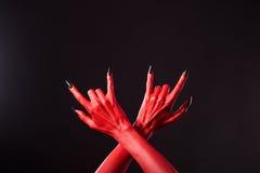 Mãos do diabo vermelho que mostram o gesto do metal pesado Imagens de Stock
