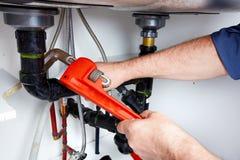 Mãos do encanador com uma chave. Fotos de Stock
